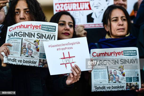 Protesters hold copies of Turkish daily newspaper Cumhuriyet and placards during a demonstration in front of a courthouse in Istanbul on October 31...