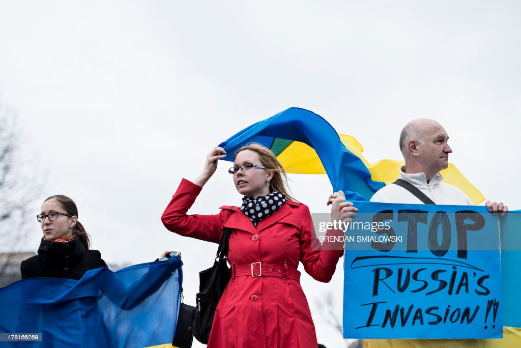 Protesters hold flags and signs outside the White House during an anti-Putin protest March 12, 2014 in Washington, DC ahead of meetings between US President Barack Obama and Ukrainian Prime Minister Arseniy Yatsenyuk. Leading world powers in the Group of Seven warned Wednesday against Russia's 'annexation' of Crimea as the Ukrainian premier prepared to seek President Obama's help against the Kremlin's expansionist threat. AFP PHOTO/Brendan SMIALOWSKI