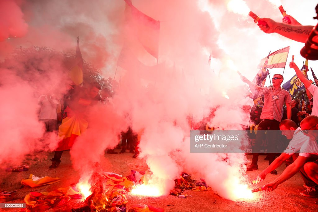 Protesters hold flares and burn 'Esteladas' Catalan pro-independence flags during an ultra-right wing anti-separatist demonstration for the unity of Spain called by 'Falange Espanola' during the Spanish National Day (Dia de la Hispanidad) in Barcelona on October 12, 2017. Spain marks its national day today with a show of unity in the face of Catalan independence efforts, a day after the central government gave the region's separatist leader a deadline to abandon his secession bid. The country is suffering its worst political crisis in a generation after separatists in the wealthy northeastern region voted in a banned referendum on October 1 to split from Spain BARRENA