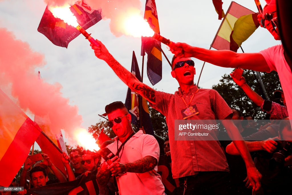 Protesters hold flares during an ultra-right wing anti-separatist demonstration for the unity of Spain called by 'Falange Espanola' during the Spanish National Day (Dia de la Hispanidad) in Barcelona on October 12, 2017. Spain marks its national day today with a show of unity in the face of Catalan independence efforts, a day after the central government gave the region's separatist leader a deadline to abandon his secession bid. The country is suffering its worst political crisis in a generation after separatists in the wealthy northeastern region voted in a banned referendum on October 1 to split from Spain BARRENA