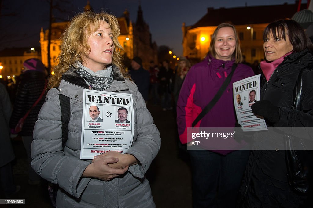 Protesters hold flyers with images of Slovenian Prime Minister Janez Jansa (L) and mayor of Ljubljana Zoran Jakovic as 'wanted' criminals during a demonstration against political corruption and the Prime Minister in Ljubljana, on January 11, 2013. Several thousand people in Slovenia's capital today joined in one of the biggest anti-government rallies in recent months, demanding the resignation of Prime Minister Janez Jansa, who has been accused of corruption. State radio estimated over 10,000 people took part in the protest called by civil groups under the slogan 'For the government's resignation and the renewal of Slovenia.' Police put the figure closer to 8,000. AFP PHOTO / Jure Makovec