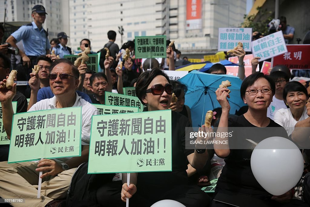 Protesters hold ginger during a rally organised by Journalist groups to protest the sacking of Ming Pao's Executive Chief Editor Keung Kwok-yuen in Hong Kong on May 2, 2016 -- the ginger represents courage and a play on words of Mr Keung surname. / AFP / ISAAC