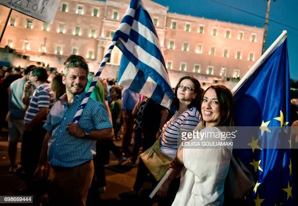 Protesters hold Greek and EU flags as they gather in front of the Greek Parliament in Athens on June 20 during a demonstration against the country's...
