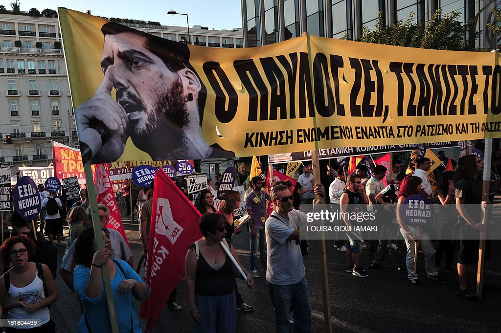 Protesters hold on September 25, 2013 a banner featuring a picture of the murdered anti-fascist musician, 34-year-old musician Pavlos Fyssas, and reading: 'Pavlos lives, crack the fascists', during a massive demonstration in Athens heading toward the offices of the neo-Nazi party Golden Dawn. Greek Police clashed with protesters in Athens late September 25 at the end of a huge march sparked by the murder of an anti-fascist musician, allegedly at the hands of a self-confessed neo-Nazi. Protesters were seen hurling petrol bombs at riot police, who responded with tear gas a few hundred meters (yards) from the headquarters of the Golden Dawn. AFP PHOTO / LOUISA GOULIAMAKI
