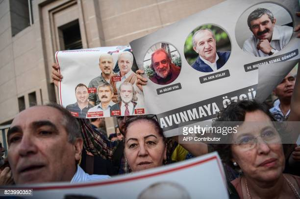 TOPSHOT Protesters hold pictures of Cumhuriyet journalists during a demonstration in Istanbul on July 28 2017 after a Turkish court ordered the...