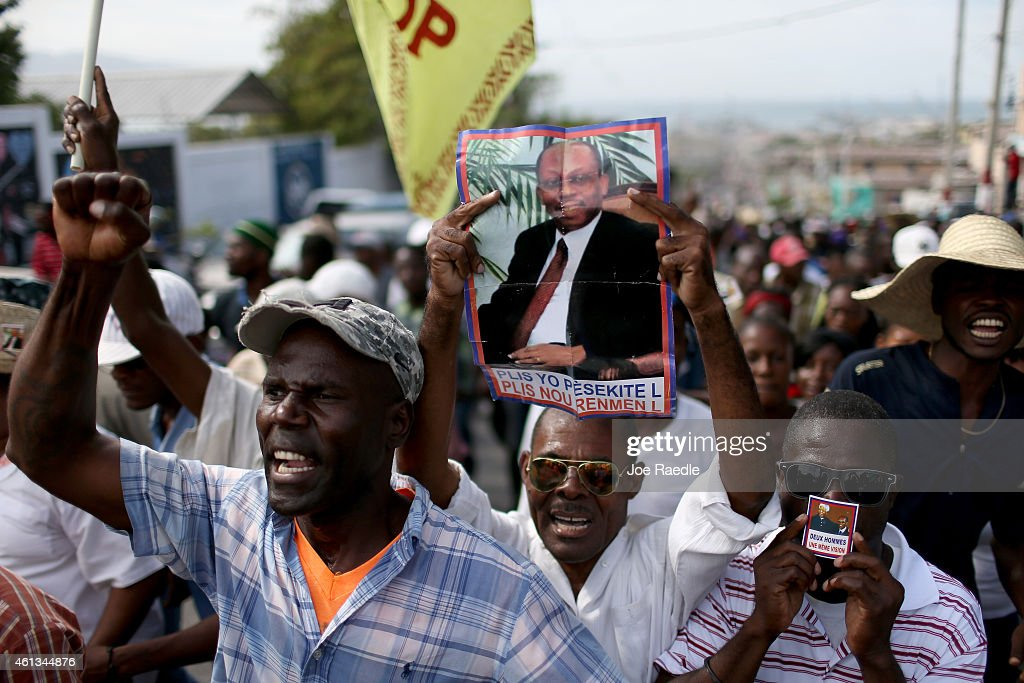 Protesters hold pictures of former Haitian President <a gi-track='captionPersonalityLinkClicked' href=/galleries/search?phrase=Jean-Bertrand+Aristide&family=editorial&specificpeople=176717 ng-click='$event.stopPropagation()'>Jean-Bertrand Aristide</a> as they make their voices heard in opposition to current Haitian President Michel Martelly who is locked in a stalemate over parlimentary elections on January 11, 2015 in Port-au-Prince, Haiti. The day before the anniversary of the magnitude 7.0 earthquake that struck just before 5 p.m. on Jan. 12, 2010, destroying buildings and killing as many as 316,000 people, protesters are asking the government to hold elections and for the president to step down after the elections have been delayed for over three years.
