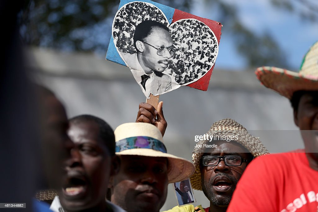 Protesters hold pictures of former Haitian President Jean-Bertrand Aristide as they make their voices heard in opposition to current Haitian President Michel Martelly who is locked in a stalemate over parlimentary elections on January 11, 2015 in Port-au-Prince, Haiti. The day before the anniversary of the magnitude 7.0 earthquake that struck just before 5 p.m. on Jan. 12, 2010, destroying buildings and killing as many as 316,000 people, protesters are asking the government to hold elections and for the president to step down after the elections have been delayed for over three years.