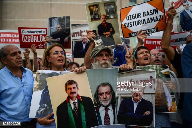 Protesters hold pictures of jailed Cumhuriyet journalists along with signs reading 'Free media cannot be silenced' during a demonstration against...
