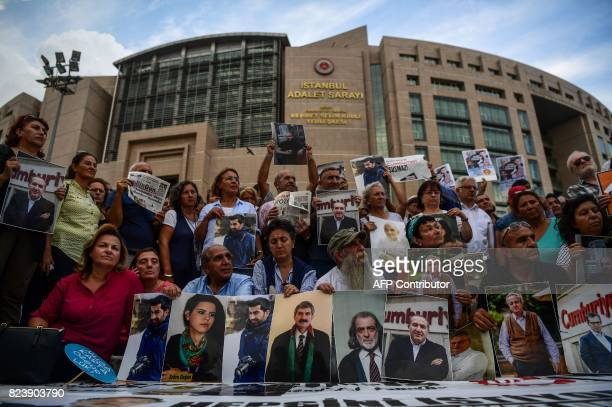 TOPSHOT Protesters hold pictures of jailed Cumhuriyet journalists during a demonstration against their arrest outside the courthouse of Istanbul on...