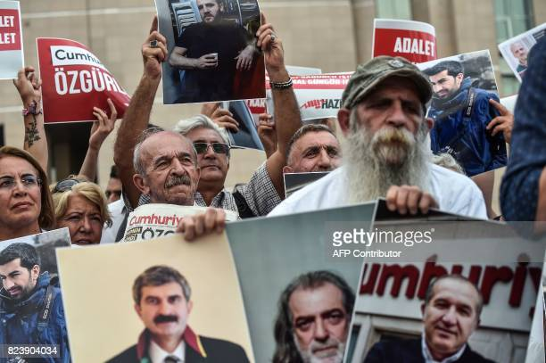 Protesters hold pictures of jailed Cumhuriyet journalists during a demonstration against their arrest outside the courthouse of Istanbul on July 28...
