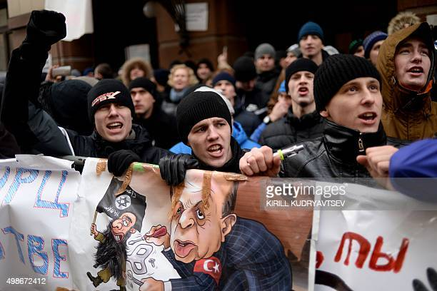 Protesters hold placards and shout slogans as they take part in an antiTurkey picket outside the Turkish embassy in Moscow on November 25 2015 Turkey...