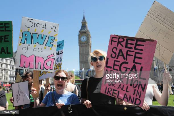 Protesters hold placards as they attend a demonstration against the Conservative party alliance with the DUP in Parliament Square on June 10 2017 in...