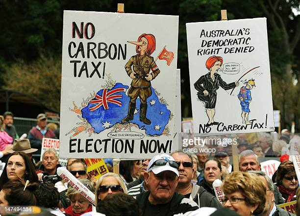 Protesters hold placards as they attend a no carbon tax rally in Sydney on July 1 2012 Australia on July 1 introduced a controversial carbon tax in a...