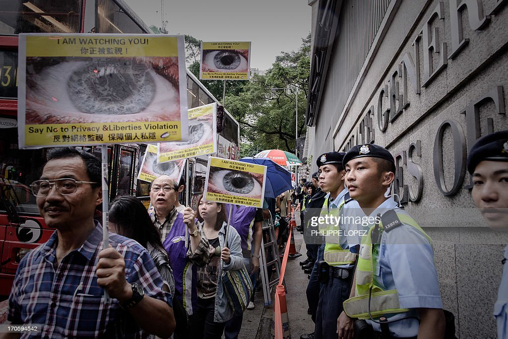 Protesters hold placards as they march along the US consulate in support of former US spy Edward Snowden in Hong Kong on June 15, 2013. Snowden, a former CIA technical assistant, is in hiding in Hong Kong after he arrived in the city on May 20 and blew the lid on a vast electronic surveillance operation by the National Security Agency, which has hit targets in China and Hong Kong. AFP PHOTO / Philippe Lopez