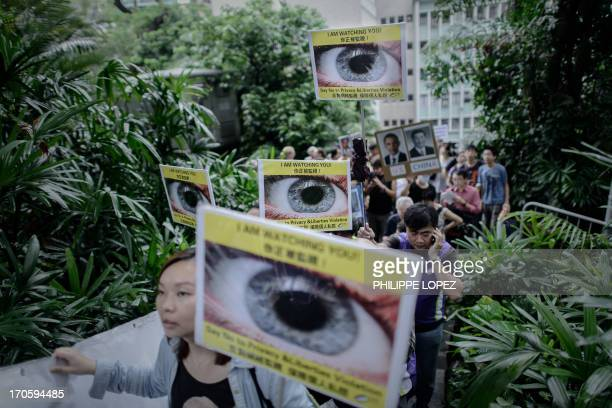 Protesters hold placards as they march to the US consulate in support of Edward Snowden from the US in Hong Kong on June 15 2013 Snowden a former CIA...
