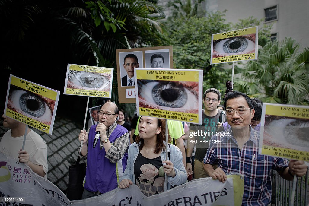 Protesters hold placards as they march to the US consulate in support of Edward Snowden from the US in Hong Kong on June 15, 2013. Snowden, a former CIA technical assistant, is in hiding in Hong Kong after he arrived in the city on May 20 and blew the lid on a vast electronic surveillance operation by the National Security Agency, which has hit targets in China and Hong Kong. AFP PHOTO / Philippe Lopez