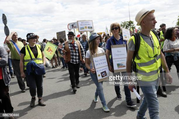 Protesters hold placards during a demonstration against 'EuropaCity' a project of a giant commercial and leisure complex developed by Auchan retail...