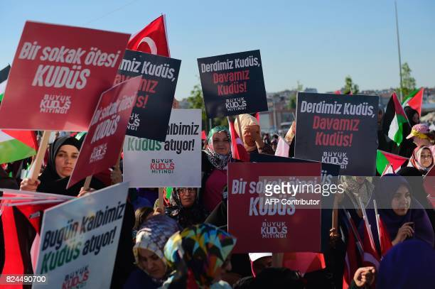 Protesters hold placards during a demonstration in Istanbul on July 30 to protest against measures taken by Israel in Jerusalem and to show...