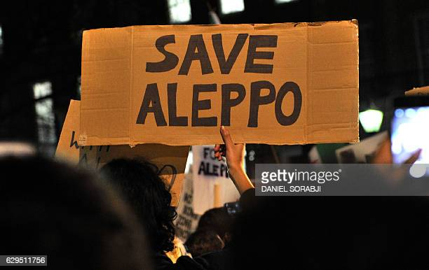 Protesters hold placards during a demonstration in solidarity with the inhabitants of the embattled Syrian city of Aleppo outside the entrance to...