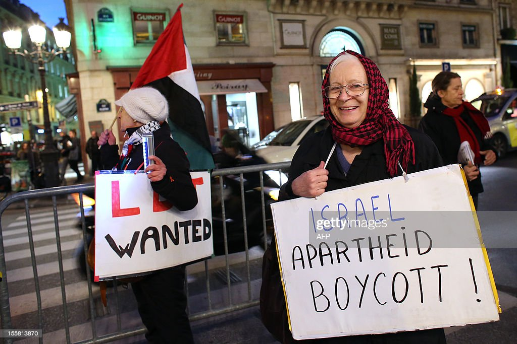 Protesters hold placards during a demonstration with about 120 members of the 'Indigenous of the Republic's Party' (PIR), on November 8, 2012 in front of France's Justice Ministry in Paris, to claim the dissolution of the Jewish Defence League (LDJ), as they accuse this jewish organisation of far-right attacks on pro-Palestinian supporters. On October 25, the LDJ uploaded on Youtube website a video showing PIR's spokeswoman Houria Bouteldja and pro-Palestinian militants Olivia Zemor and Jacob Cohen, sprayed with red paint after being assaulted by LDJ members.