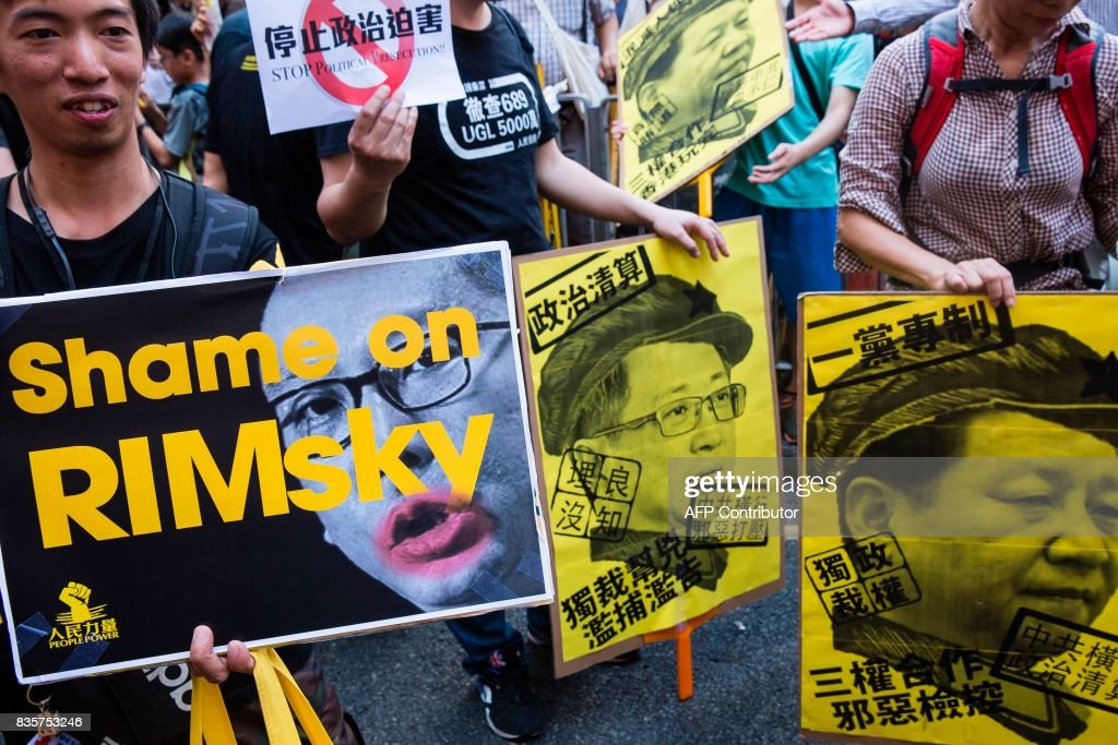 Protesters hold placards during a march in Hong Kong on August 20, 2017, to protest the jailing of Joshua Wong, Nathan Law and Alex Chow (not pictured), the leaders of Hong Kong's 'Umbrella Movement', after their sentencing at the High Court on August 17. Wong, Law and Chow were handed sentences of six to eight months by the Court of Appeal for their role in 2014's massive Umbrella Movement protests, which called for fully free leadership elections and were an unprecedented challenge to Beijing. /