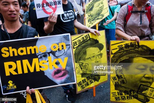 Protesters hold placards during a march in Hong Kong on August 20 to protest the jailing of Joshua Wong Nathan Law and Alex Chow the leaders of Hong...