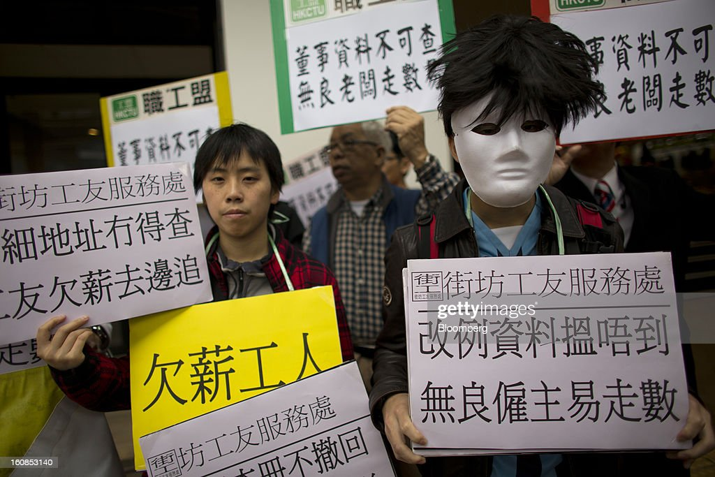 "Protesters hold placards during a march organized by labor unions in Hong Kong, China, on Thursday, Feb. 7, 2013. The Financial Services and the Treasury Bureau and the city's Companies Registry put forward a proposal to ""enhance protection of the privacy of personal information,"" in November as part of a consultation paper on a new companies ordinance. The proposed amendments would make tracing the personal details of company directors in the city more difficult. Photographer: Lam Yik Fei/Bloomberg via Getty Images"