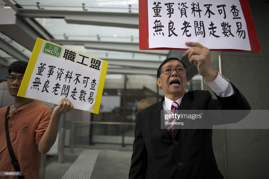 """Protesters hold placards during a march organized by labor unions in Hong Kong, China, on Thursday, Feb. 7, 2013. The Financial Services and the Treasury Bureau and the city's Companies Registry put forward a proposal to """"enhance protection of the privacy of personal information,"""" in November as part of a consultation paper on a new companies ordinance. The proposed amendments would make tracing the personal details of company directors in the city more difficult. Photographer: Lam Yik Fei/Bloomberg via Getty Images"""