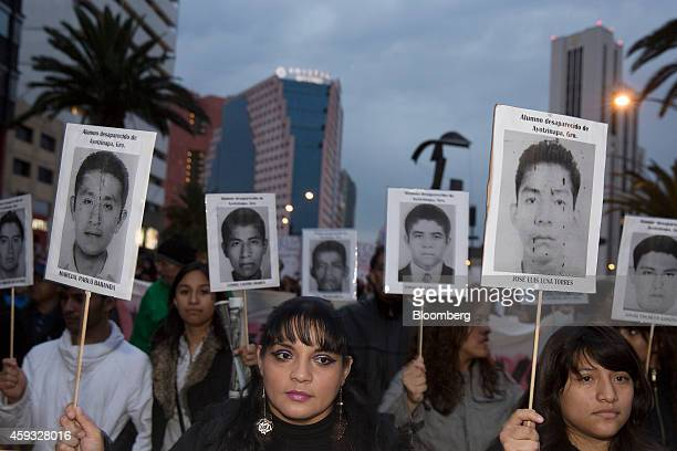 Protesters hold placards during a march to central square known as the Zocalo to protest at the government's response to the mass disappearance of 43...