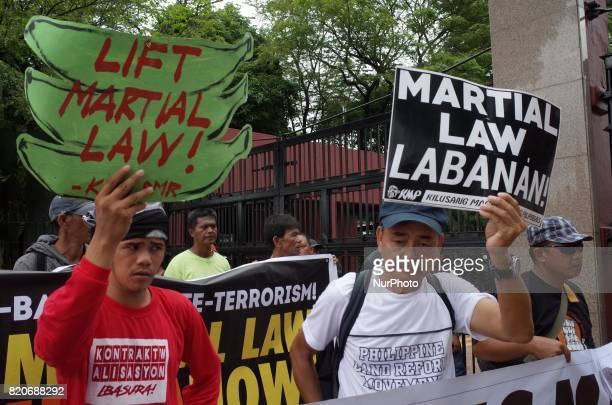 Protesters hold placards during a rally coinciding the joint session on Martial Law extension outside the House of Representatives in Quezon City...