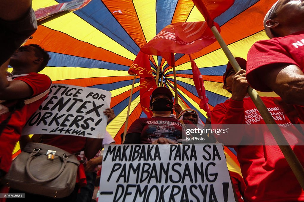 Protesters hold placards during a rally commemorating Labor Day in Manila on Sunday, May 1, 2016. Thousands of protesters marched to protest the government's labour policy and demand higher wages amid rising prices for basic commodities.