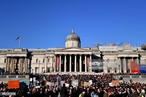 Protesters hold placards during the Women's March in Trafalgar Square in London on January 21 2017 as part of a global day of protests against new US...