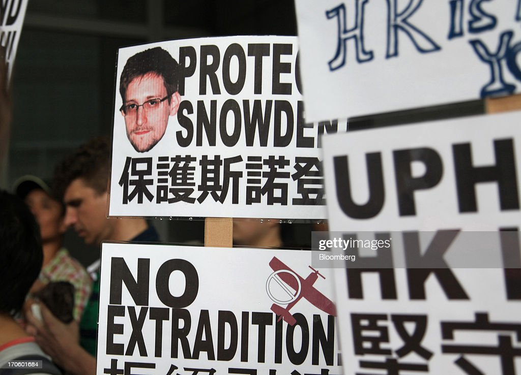 Protesters hold placards outside government headquarters during a rally in support of Edward Snowden, the former National Security Agency contractor, in Hong Kong, China, on Saturday, June 15, 2013. Protesters marched to Hong Kongs government headquarters demanding their leaders protect Edward Snowden, who fled to the city after exposing a U.S. surveillance program. Photographer: Luke Casey/Bloomberg via Getty Images