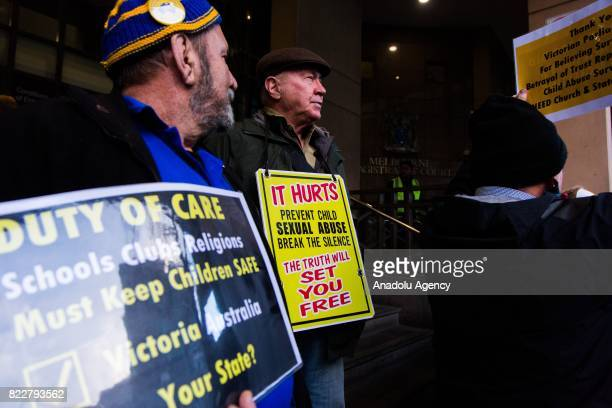Protesters hold placards outside the court during Cardinal George Pell's court hearing at the Melbourne Magistrates Court in Melbourne Australia on...