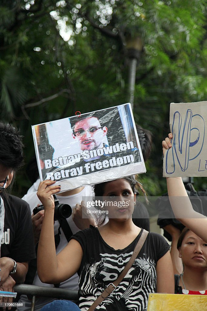 Protesters hold placards outside the U.S. consulate during a rally in support of <a gi-track='captionPersonalityLinkClicked' href=/galleries/search?phrase=Edward+Snowden&family=editorial&specificpeople=10983676 ng-click='$event.stopPropagation()'>Edward Snowden</a>, the former National Security Agency contractor, in Hong Kong, China, on Saturday, June 15, 2013. Protesters marched to Hong Kongs government headquarters demanding their leaders protect <a gi-track='captionPersonalityLinkClicked' href=/galleries/search?phrase=Edward+Snowden&family=editorial&specificpeople=10983676 ng-click='$event.stopPropagation()'>Edward Snowden</a>, who fled to the city after exposing a U.S. surveillance program. Photographer: Luke Casey/Bloomberg via Getty Images