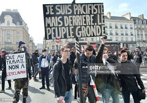 Protesters hold placards reading 'I am a pacifist but the people behind are rumbling' and 'Yes at work no to slavery' during a demonstration against...