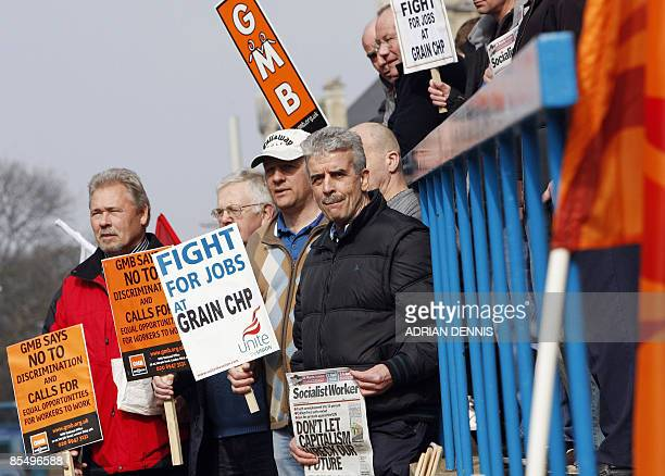 Protesters hold placards while holding a demonstration about a labour dispute outside the Job Centre in Chatham in southeast England on March 19 2009...