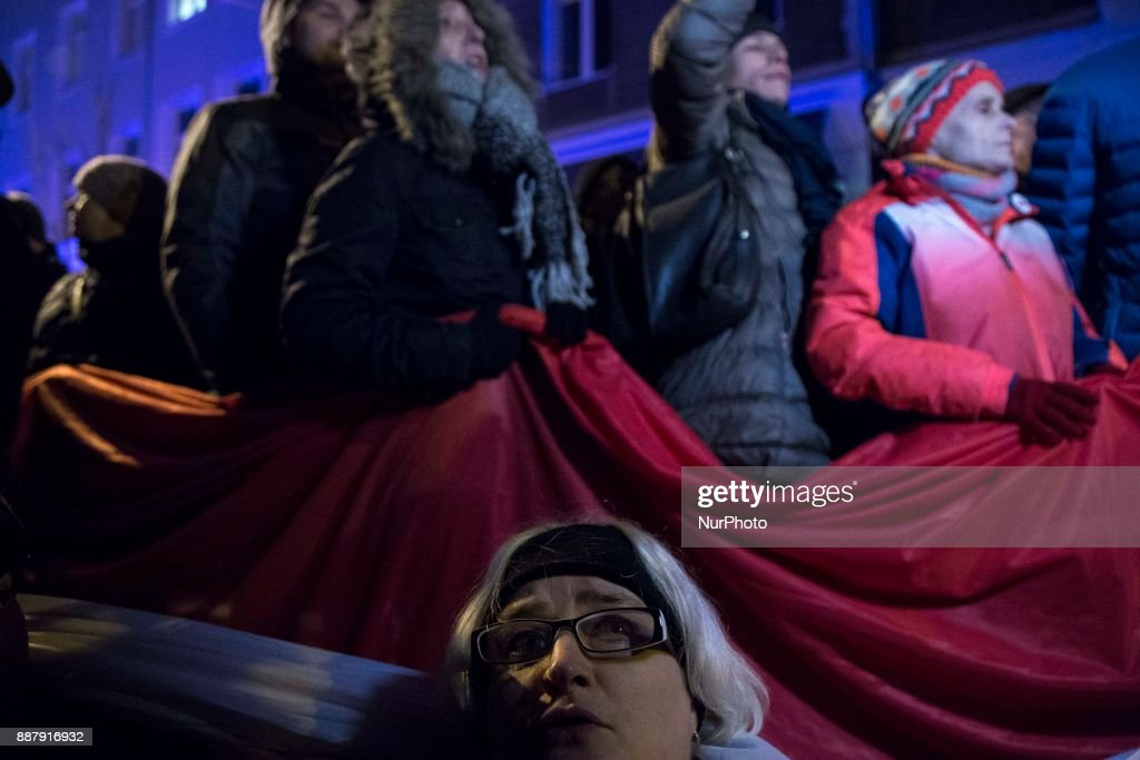 Protesters hold polish flag during illegal demonstration near Polish parliament organized by opposition group Obywatele RP in Warsaw on December 7, 2017.