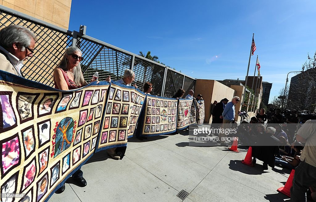 Protesters hold quilts bearing portraits of young children outside the Cathedral of Our Lady of the Angels in Los Angeles, California, on February 1, 2013, one day after the release of personnel files of priests accused of sexual misconduct. The archbishop of Los Angeles Jose Gomez stripped his predecessor, retired Cardinal Roger Mahony, of all church duties on January 31. In all, 124 files were released on the Los Angeles archdiocese's website, listed by priests' names, including 82 containing information on allegations of childhood sexual abuse.. AFP PHOTO / Frederic J. BROWN