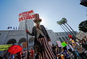 Protesters hold signs after a march to Los Angeles City Hall during the 'Occupy Los Angeles' demonstration in solidarity with the ongoing 'Occupy...