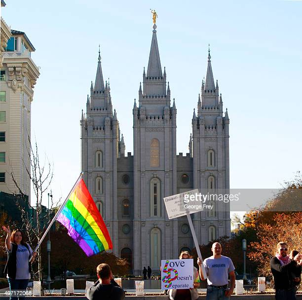 Protesters hold signs and a pride flag in front of the historic Mormon temple after many submitted their resignations from the Church of Jesus Christ...