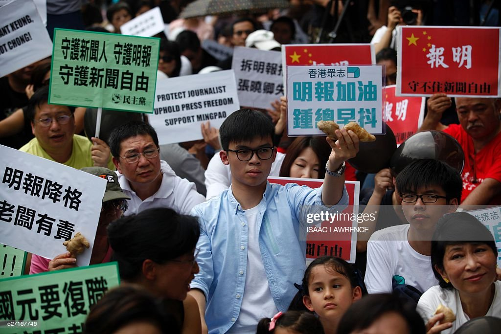 Protesters hold signs as they gather outside the offices of Ming Pao during a rally organised by Journalist groups to protest the sacking of Ming Pao's Executive Chief Editor Keung Kwok-yuen in Hong Kong on May 2, 2016. / AFP / ISAAC