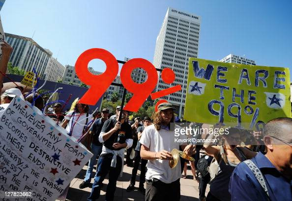 Protesters hold signs as they march to Los Angeles City Hall during the 'Occupy Los Angeles' demonstration in solidarity with the ongoing 'Occupy...