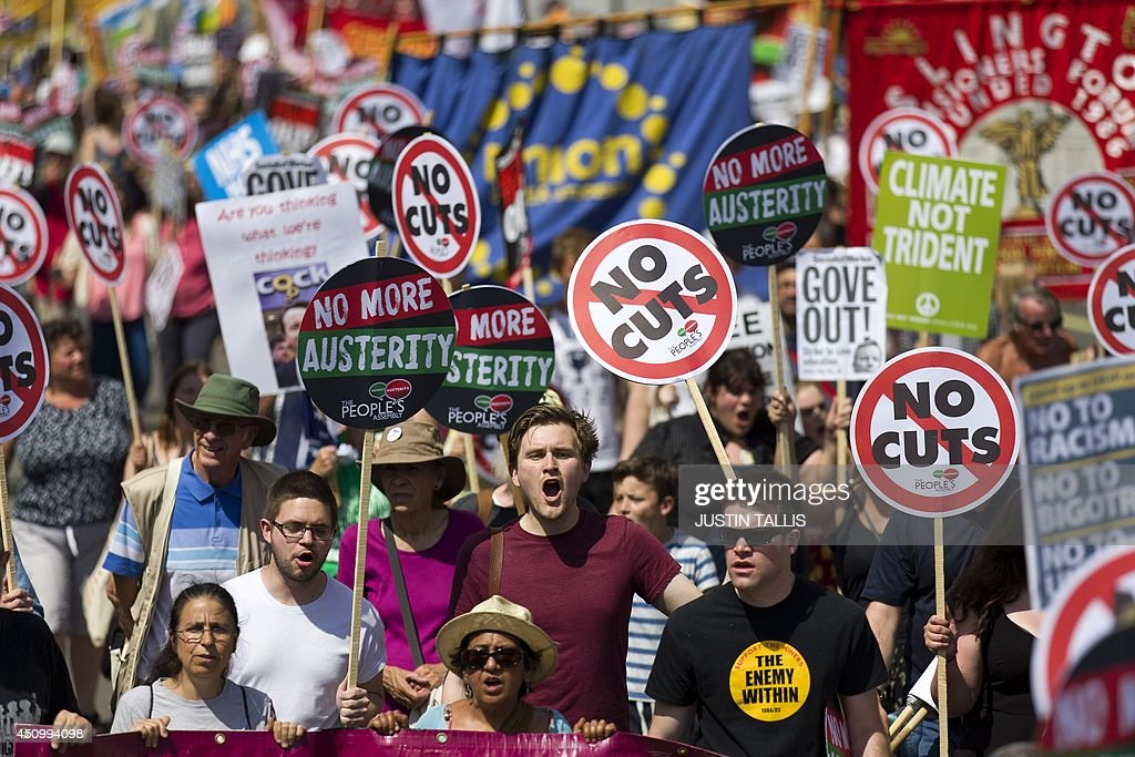Protesters hold signs as they protest against government austerity measures in Parliament Square in London on June 21 2014 The demonstration is...