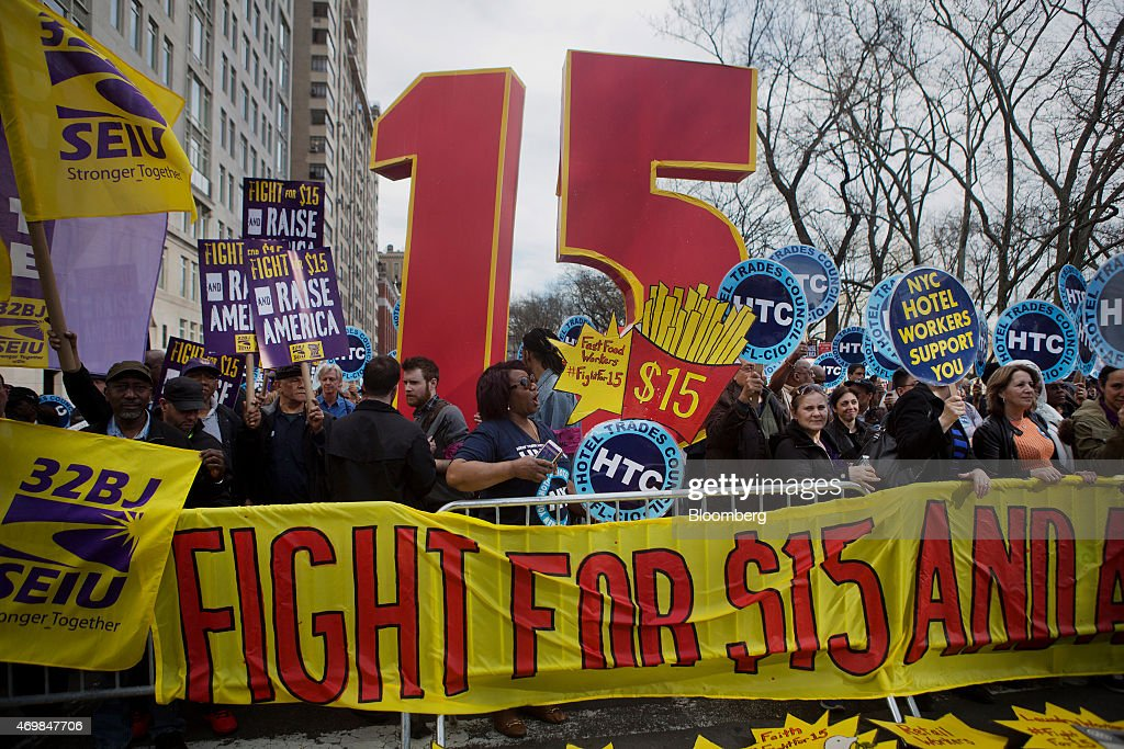 Protesters hold signs at a rally in support of minimum wage increase in New York US on Wednesday April 15 2015 Fastfood workers held rallies in 236...