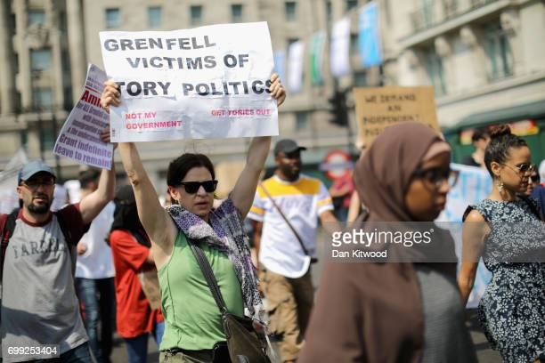 Protesters hold signs calling for justice for the victims of the Grenfell Disaster as they march towards Westminster during an antigovernment protest...