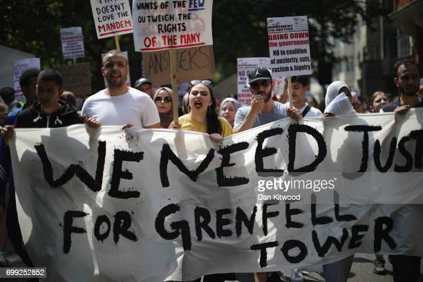 Protesters hold signs calling for justice for the victims of the Grenfell Disaster and shout slogans as they march towards Westminster during an...