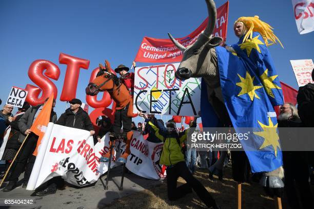 Protesters hold signs during a demonstration against the Transatlantic Trade and Investment Partnership and EUCanada Comprehensive Economic and Trade...