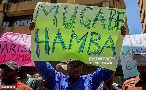 Protesters hold signs during a demonstration by opposition parties against the introduction of bond notes as a currency in Harare on November 30 2016...