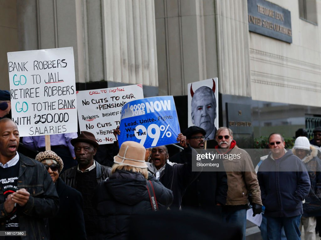 Protesters hold signs during a demonstration outside of the Theodore Levin United States Courthouse in Detroit, Michigan, U.S., on Monday Oct. 28, 2013. Michigan Governor Rick Snyder told a federal judge that he considers Detroits bankruptcy the 'largest issue' facing the U.S. Photographer: Jeff Kowalsky/Bloomberg via Getty Images